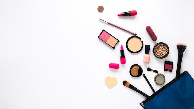 Schoonheidstas met verschillende cosmetica op witte tafel Gratis Foto