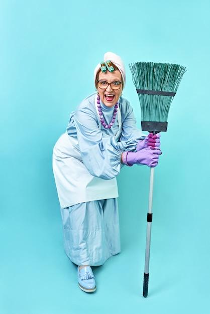 Schoonmaakster fun. bejaarde grappige huisvrouw die rond met een bezem voor de gek houdt. Premium Foto