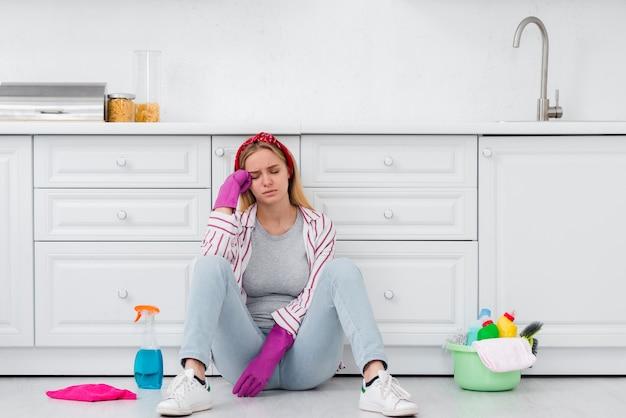 Schoonmaakster zittend op de vloer Gratis Foto