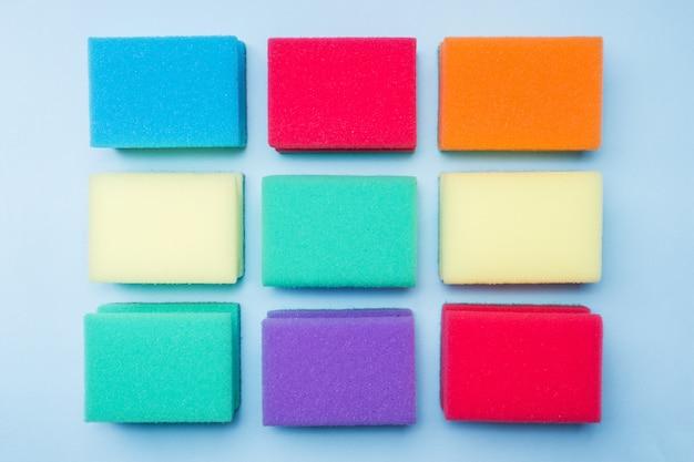 Schoonmakende kleurensponsen en borstels op blauwe achtergrond. Premium Foto