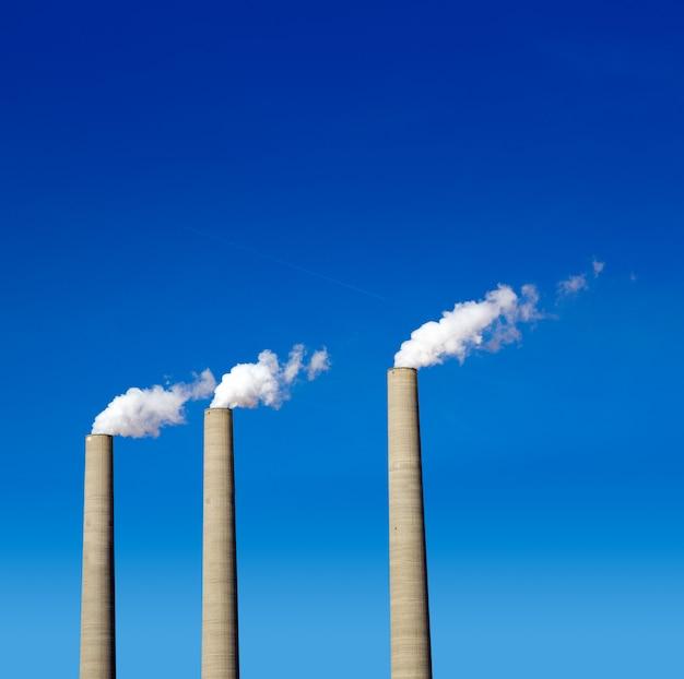 Schoorsteen witte rook drie op een rij op een blauwe hemel Premium Foto