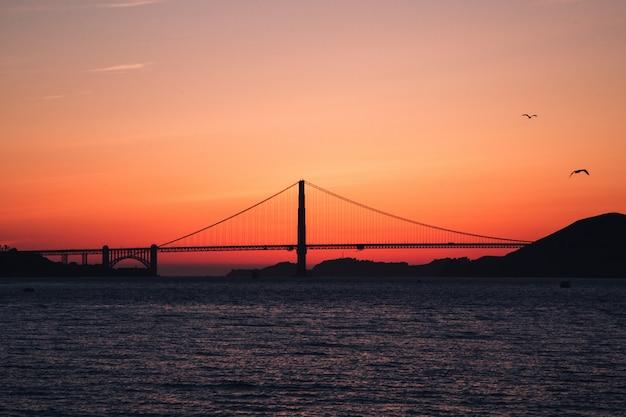 Schot van de golden gate bridge op het waterlichaam tijdens zonsondergang in san francisco, californië Gratis Foto