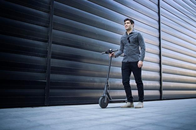Schot van de jonge knappe man die door zijn elektrische scooter op straat Gratis Foto