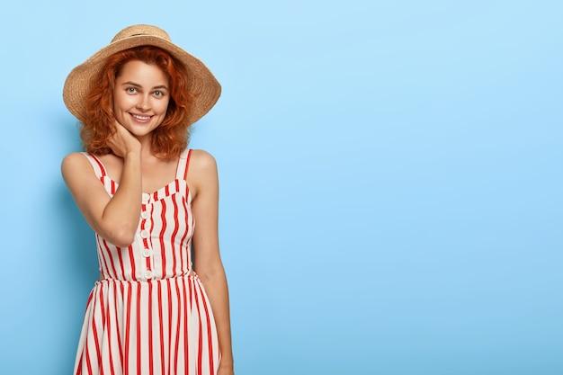 Schot van gelukkig roodharige vrouw gekleed in modieuze zomer outfit, strooien hoed, heeft charmante glimlach, natuurlijke schoonheid, staat tegen blauwe muur met lege ruimte voor uw promotie. Gratis Foto