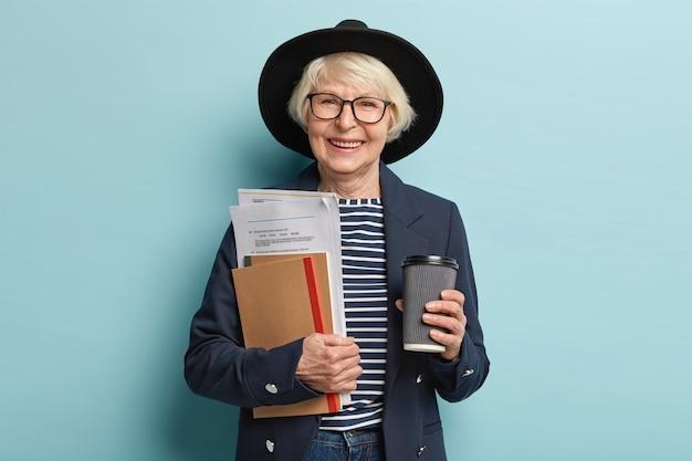 Schot van gelukkige senior ervaren zakenvrouw houdt papieren en portemonnee, drinkt afhaalmaaltijden koffie, blij om succesvol contract te ondertekenen, draagt stijlvolle hoed en jas, vormt binnen. drukke oude werker Gratis Foto