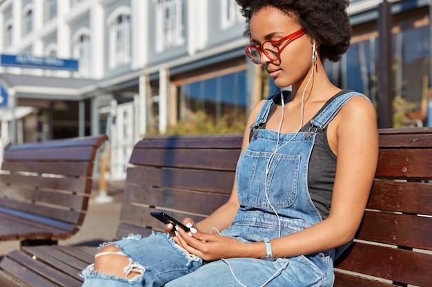 Schot van hipster meisje met donkere huid, afro kapsel, chats met volgers in sociale netwerken, luistert naar favoriete muziek in oortelefoons, besteedt vrije tijd buiten, zit op houten bankje, wacht op vriend Gratis Foto