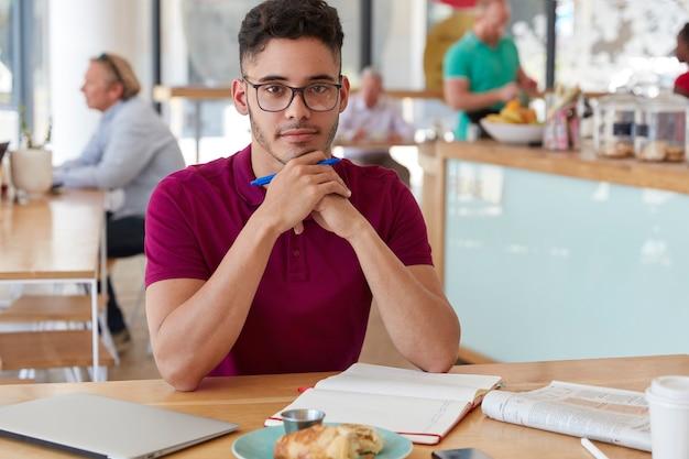 Schot van knappe ernstige gemengd ras jongeman schrijver houdt pen, maakt lijst te doen in kladblok, drinkt koffie, lunchtijd in coffeeshop alleen, bezig met werk. Gratis Foto