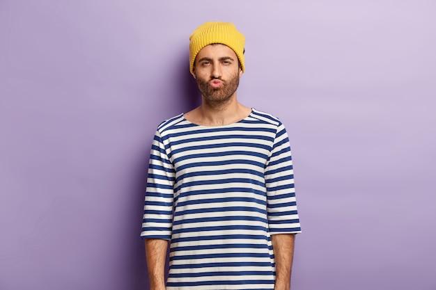 Schot van knappe jongere met borstelharen pruilt lippen en kijkt mysterieus, ontevreden over iets, draagt gele hoed en gestreepte zeeman trui Gratis Foto