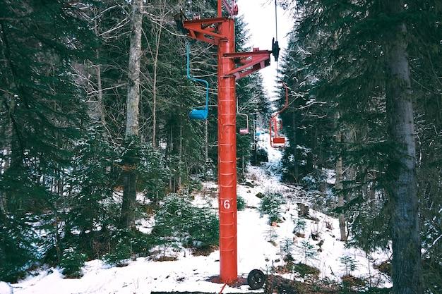 Schot van mooie oude kleine skilift met gekleurde stoelen, verplaatsen door winter woud in bergen Gratis Foto