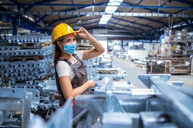 Schot van vrouw fabrieksarbeider in uniform en veiligheidshelm dragen gezichtsmasker in industriële productie-installatie Gratis Foto