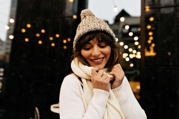 Schot van zorgeloze vrouw met lang bruin haar en charmante glimlach. Gratis Foto