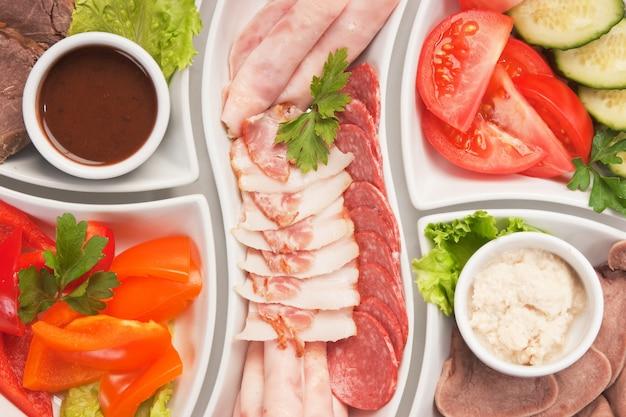 Schotel van geassorteerde worsten en groenten Premium Foto