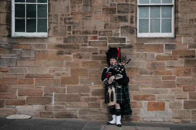 Schotse man doedelzak spelen in de straat Premium Foto