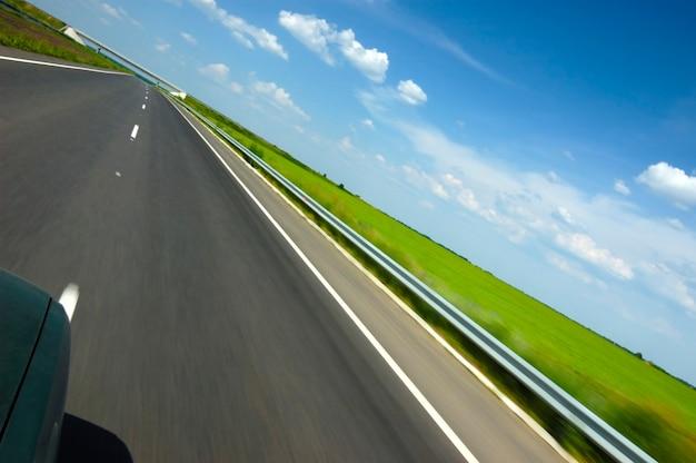 Schuine hoek shot van een gladde snelweg omgeven door mooie zomerse natuur met groen gras en blauwe lucht met bomen op een zonnige warme zomerdag Premium Foto