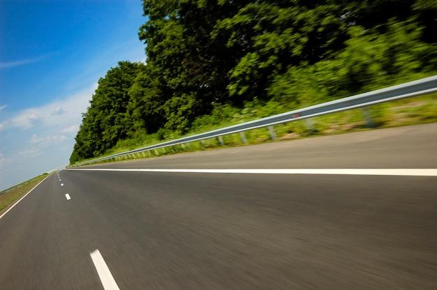Schuine hoek shot van een gladde snelweg omgeven door mooie zomerse natuur met groen gras en velden op een zonnige warme zomerdag Premium Foto