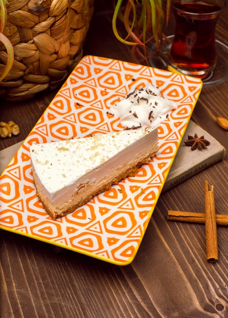 Segment van karamel vanille cheesecake op plaat tegen een rustieke bruine houten tafel Gratis Foto