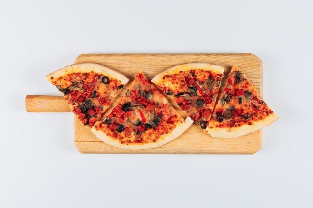 Segmenten van een pizza in een pizza bord op een helder witte gepleisterde achtergrond. plat lag. Gratis Foto