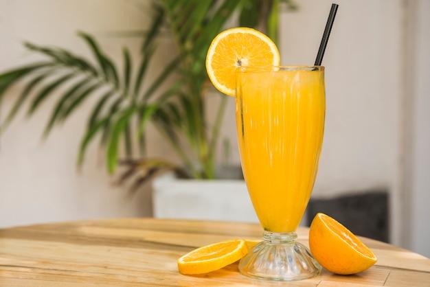 Segmenten van fruit in de buurt van glas drank met stro op tafel Gratis Foto