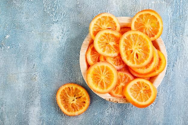 Segmenten van gedroogde sinaasappelen of mandarijnen in een houten plaat op een blauwe muur. vegetarisme en gezond eten. kopieer ruimte. plat liggen Premium Foto