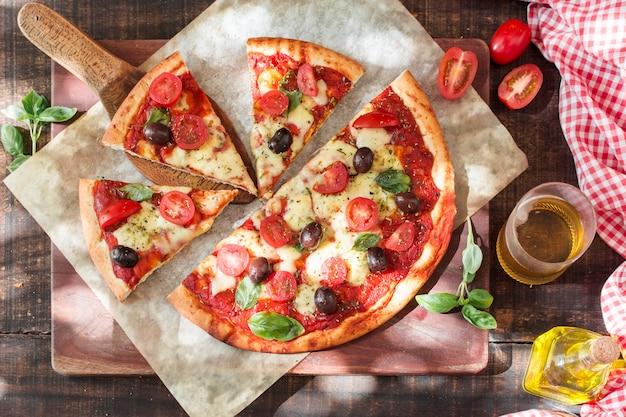 Segmenten van margherita pizza op snijplank met ingrediënten Gratis Foto