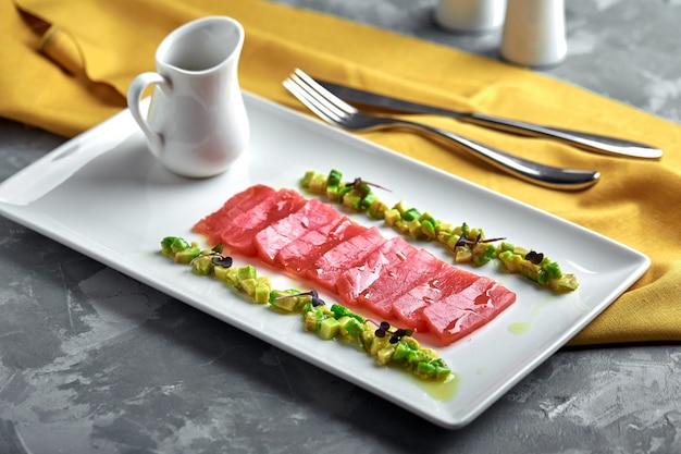 Segmenten van rauwe tonijn sashimi geserveerd op wit bord met avocado Premium Foto