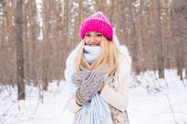 Seizoen en mensenconcept - aantrekkelijke blonde vrouw gekleed in witte jas en roze hoed die zich in een bos bevindt Premium Foto