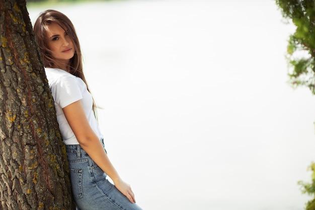 Seizoen en mensenconcept - mooie gelukkige jonge vrouw. aantrekkelijk glimlachend jong meisje die jeanskleren dragen die tijd in openlucht doorbrengen bij het park, die op een boom leunen. horizontaal Premium Foto