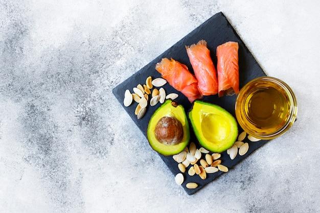 Selectie van gezonde vetbronnen, avocado, zalm, noten, olijfolie op een zwarte plaat. het concept van gezond eten. bovenaanzicht, kopie ruimte, grijze achtergrond Premium Foto