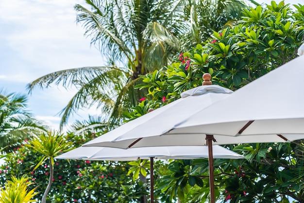 Selectief aandachtspunt op paraplu met kokospalm op de achtergrond voor vakantievakantie Gratis Foto