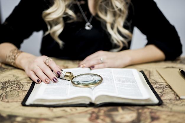 Selectief close-upschot van een persoon die een boek met een vergrootglas leest Gratis Foto