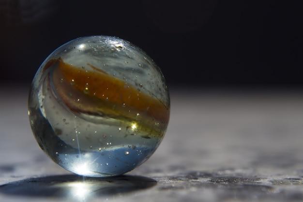 Selectieve aandacht close-up shot van een kleurrijke glazen bol bedekt met waterdruppels Gratis Foto