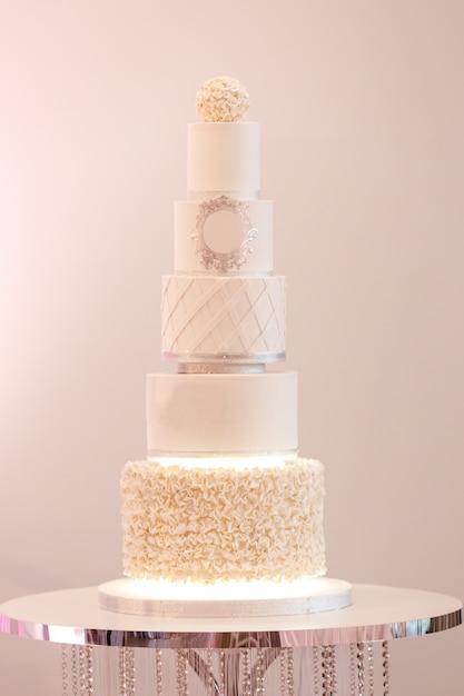 Selectieve aandacht. grote koninklijke taart in witte kleur versierd met zilveren details en witte crème op een luxe bruiloft. dessert na het feestelijke diner van de bruid en bruidegom. Premium Foto
