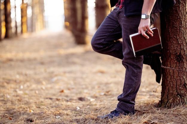 Selectieve aandacht shot van een man met een boek poseren in een bos Gratis Foto