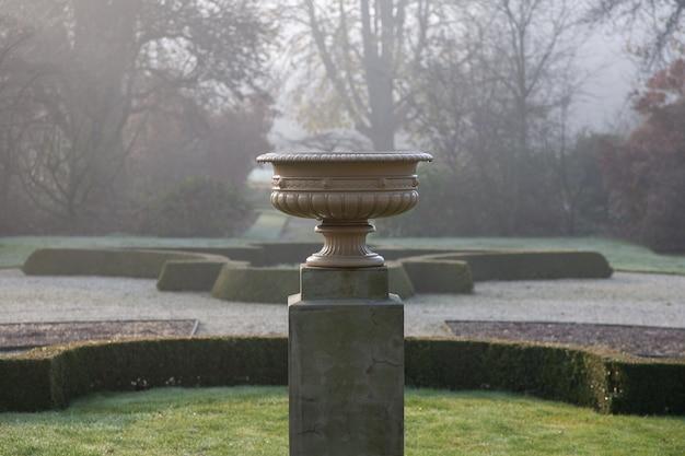 Selectieve aandacht shot van een stenen pot op een voetstuk in een park Gratis Foto