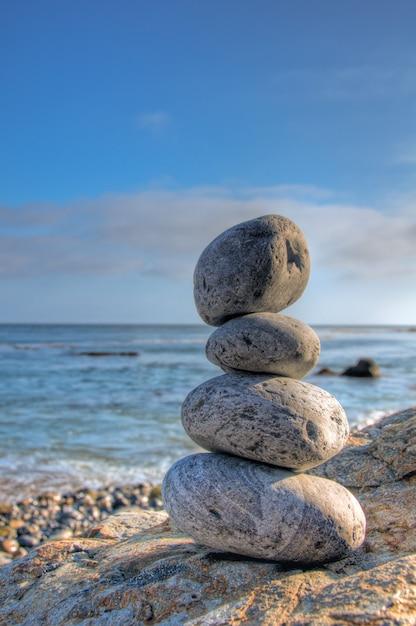 Selectieve aandacht shot van opgestapelde stenen in een kust met een wazig blauwe hemel Gratis Foto