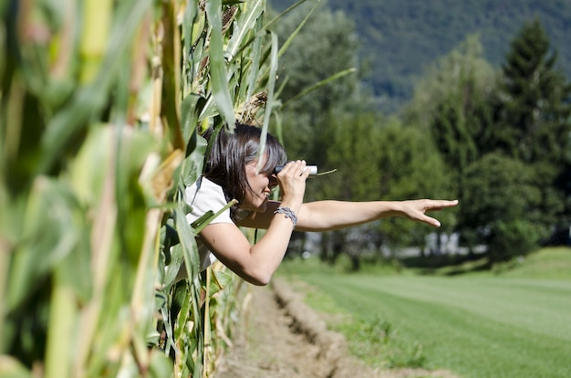 Selectieve aandacht shot van vrouwelijke kijken door een verrekijker vanuit een raam Gratis Foto