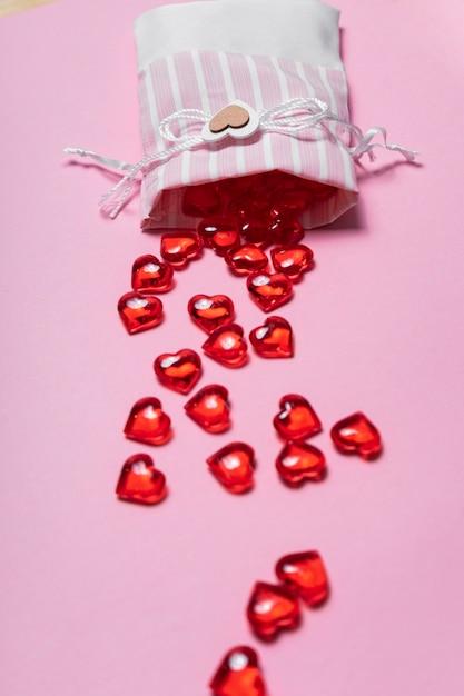 Selectieve aandacht. valentijnsdag kaart. glazen rode harten verspreid vanuit een mooie stoffen tas. het uitzicht vanaf de top. roze achtergrond Premium Foto