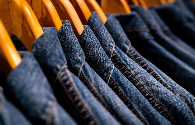 Selectieve aandacht voor jasjeans opknoping op rek in kledingwinkel. Premium Foto
