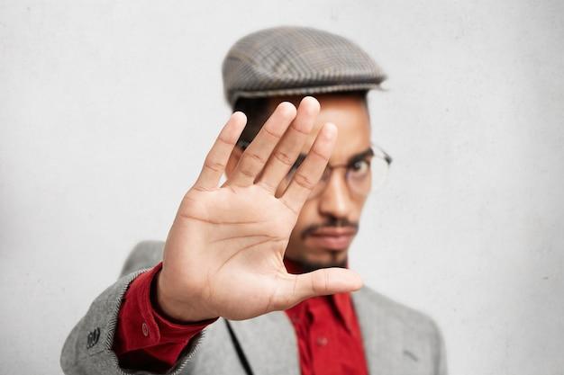 Selectieve aandacht voor palm. strikte gemengd ras man in ronde brillen, toont stopbord met hand Gratis Foto