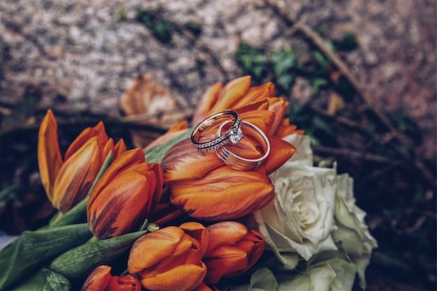 Selectieve close-up shot van zilveren diamanten ringen op oranje tulpen en witte rozen Gratis Foto