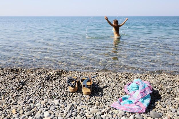 Selectieve focus op de voorgrond van de dingen van een vrouw die alleen in de zee spettert Premium Foto