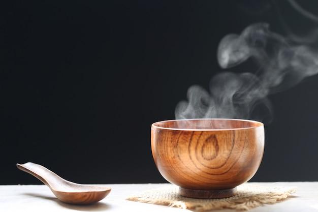 Selectieve focus van rook stijgt met hete soep in cup op donkere achtergrond. Premium Foto