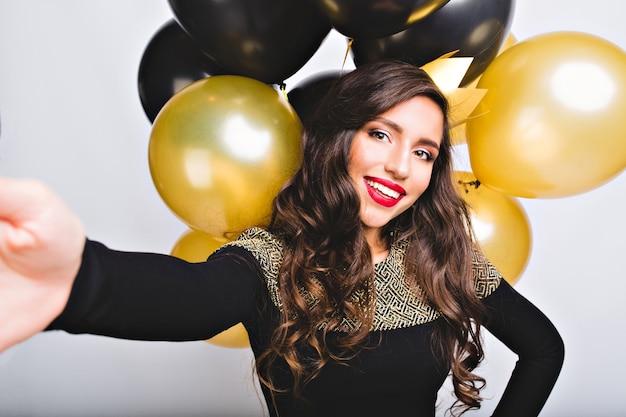 Selfie portret grappig geweldig meisje in elegante mode jurk tussen gouden en zwarte ballonnen op witte ruimte Gratis Foto