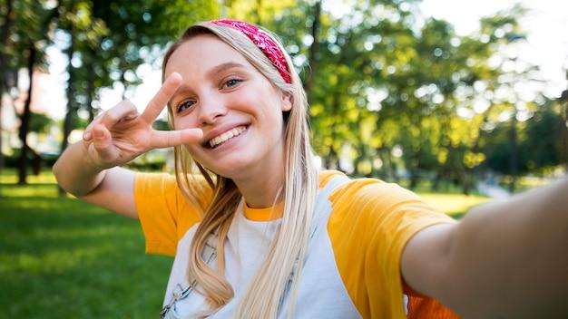 Selfie van smileyvrouw die vredesteken maakt Gratis Foto