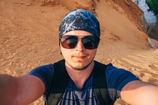Selfiemannen in een bandana op de achtergrond van zand Premium Foto