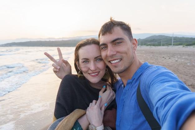 Selfiepaar verliefd op het strand bij zonsondergang met een symbool van vrede Premium Foto