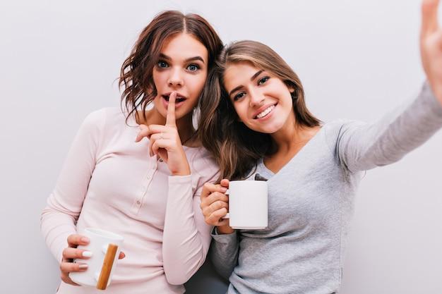 Selfieportret van twee jonge meisjes in pyjama's met kopjes op grijze muur. meisje met krullend haar legt de vinger op de lippen, ze glimlachen. Gratis Foto