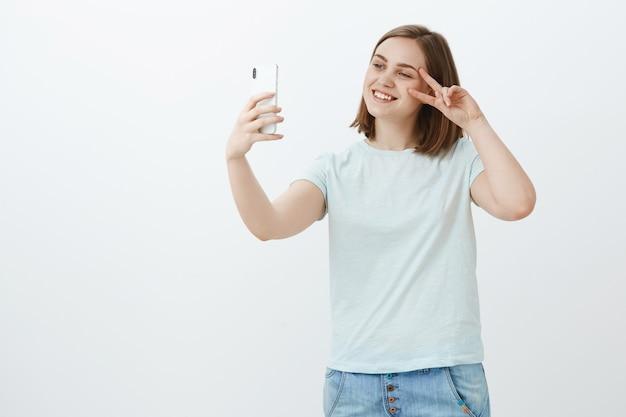 Selife-achtige methode van zelfexpressie. vriendelijk ogende sociaal en aardig europees meisje met kort bruin haar vredesteken tonen in de buurt van gezicht lachend op scherm nemen foto van zichzelf op nieuwe smartphone Gratis Foto