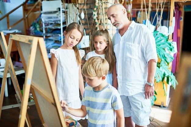 Senior art teacher met groep kinderen in studio Premium Foto