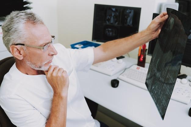 Senior arts radioloog denken aan mri-afbeeldingen. Premium Foto